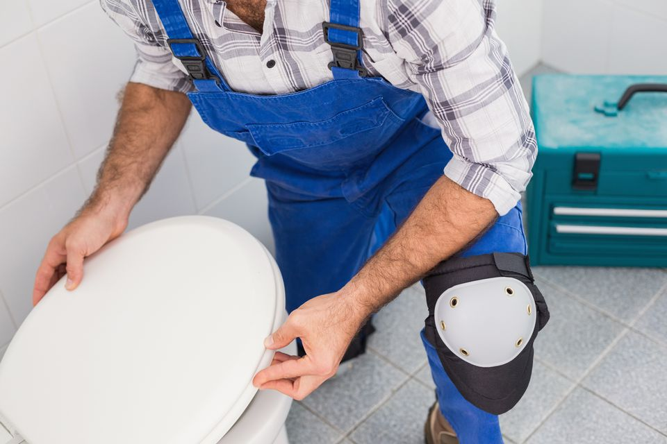 Man installing new toilet with toolbox