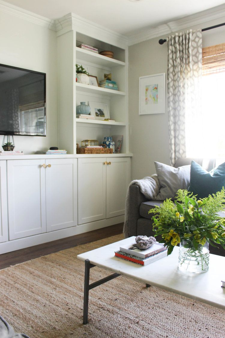 A living room with a TV and bookshelves