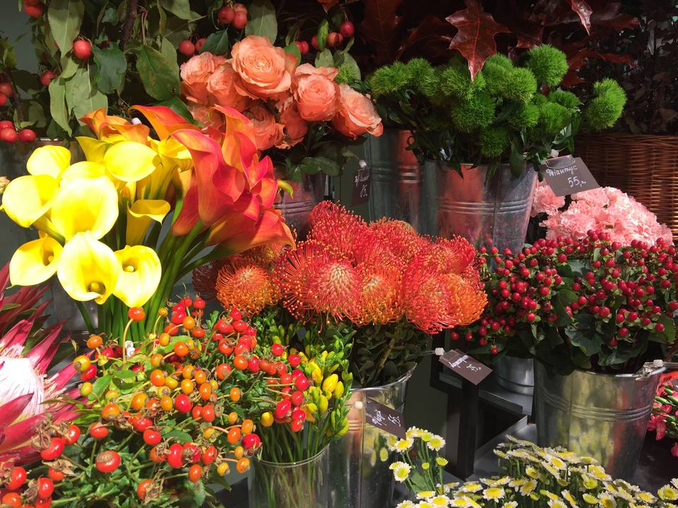 Protea, calla lilies, roses, and mums for sale at a market