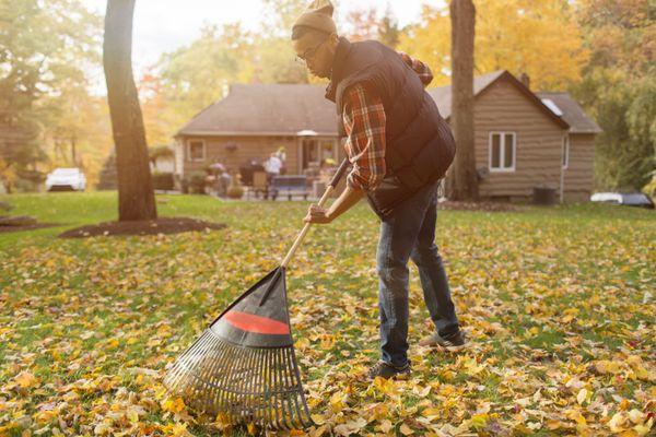 Mid adult man raking in autumn leaves garden