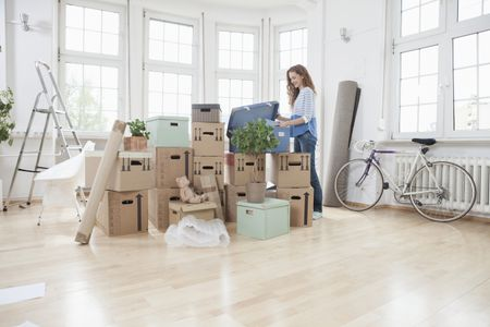 Woman In New Apartment Unng Cardboard Box