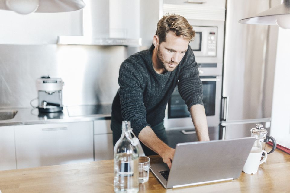 Portrait of man standing in kitchen using laptop