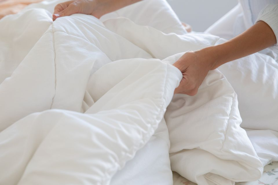 woman removing a comforter from the bed