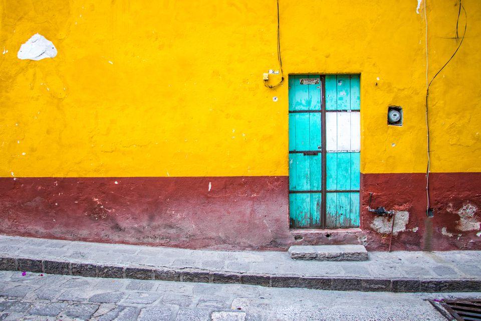 A blue door on a painted wall in San Miguel de Allende, Mexico.