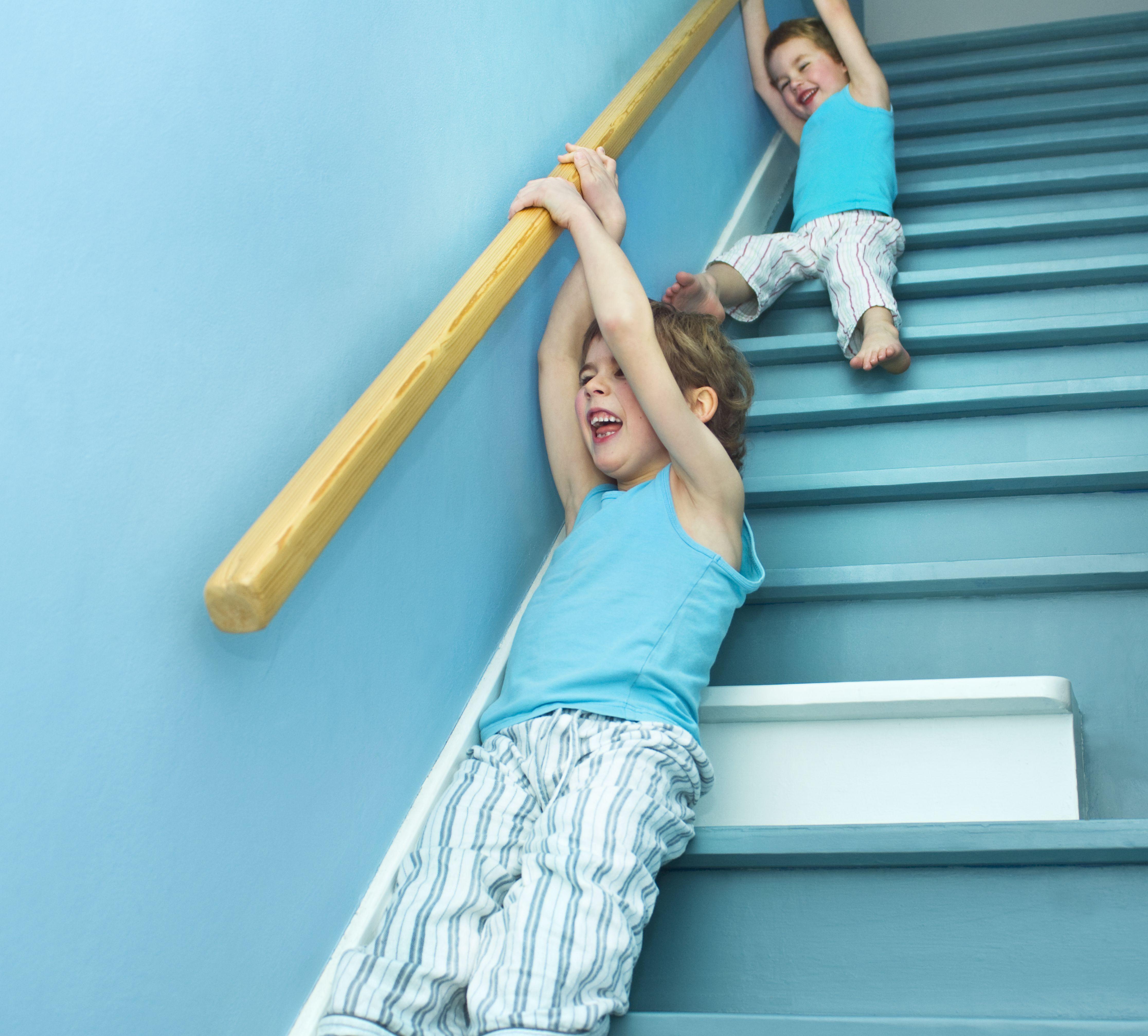 Niños deslizándose de una barandilla
