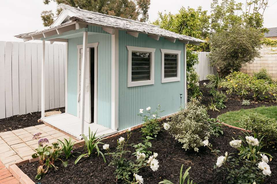 Baby blue and white outdoor shed near flower garden