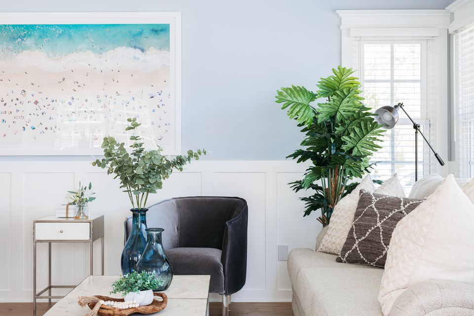 Living room with light blue and white walls with houseplants and beach-themed painting