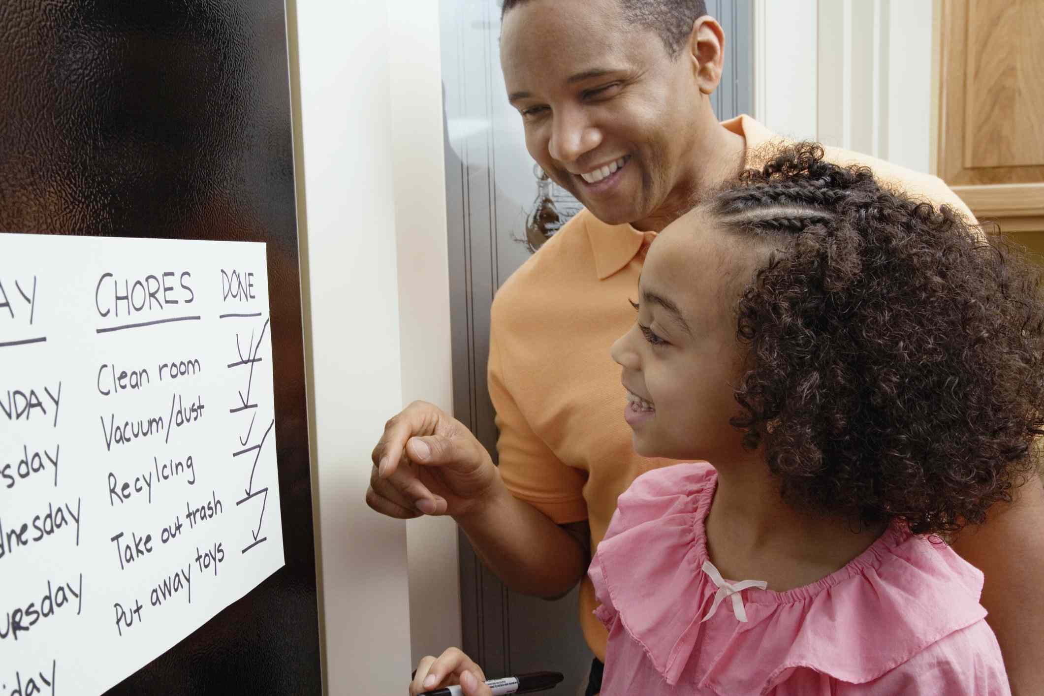 dad and daughter making a chore list