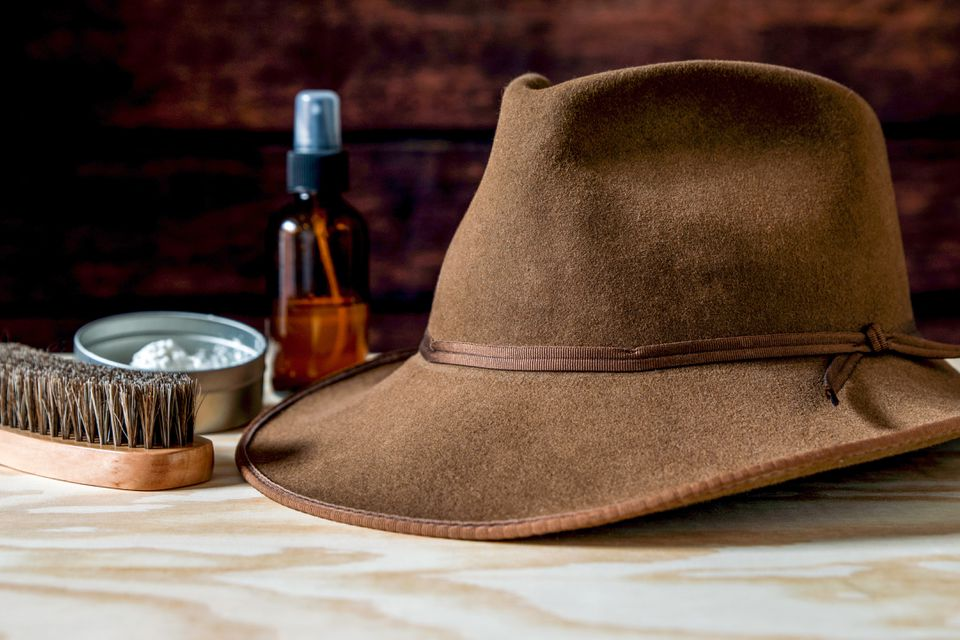 A brown felt hat with cleaning materials