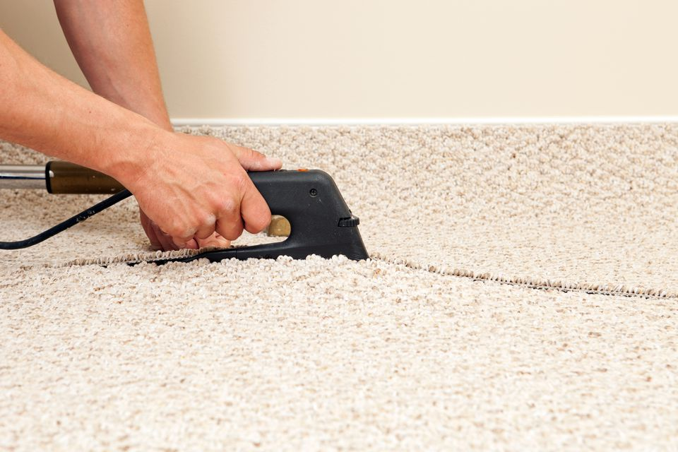 Installer Joining Two Carpet Pieces with Iron