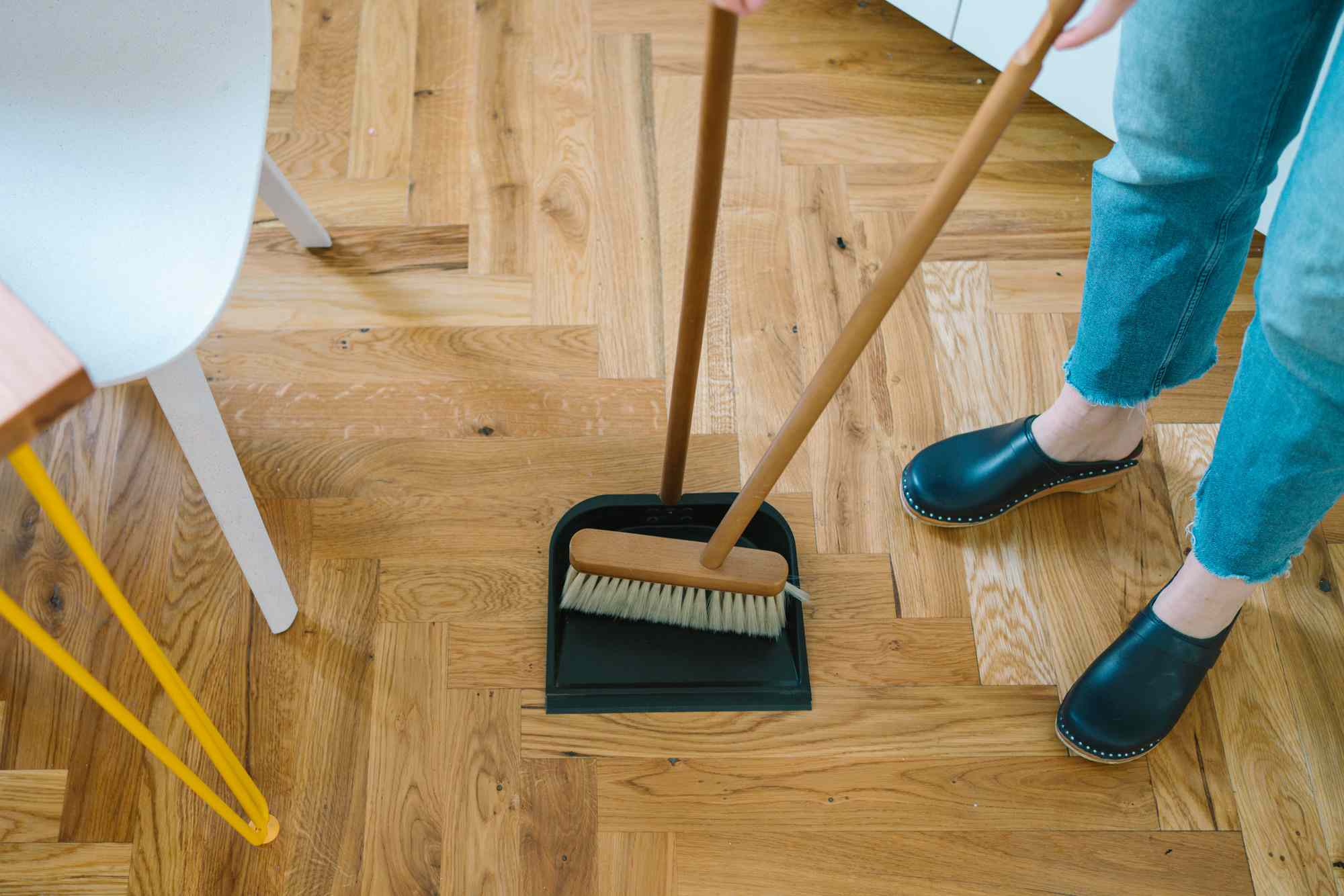 person cleaning the floor with a broom