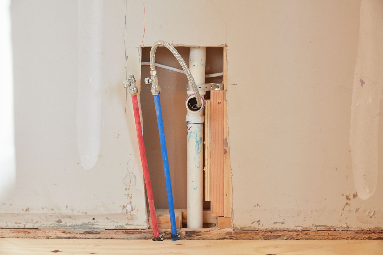 Exposed wall with plumbing pipe and blue and red wires