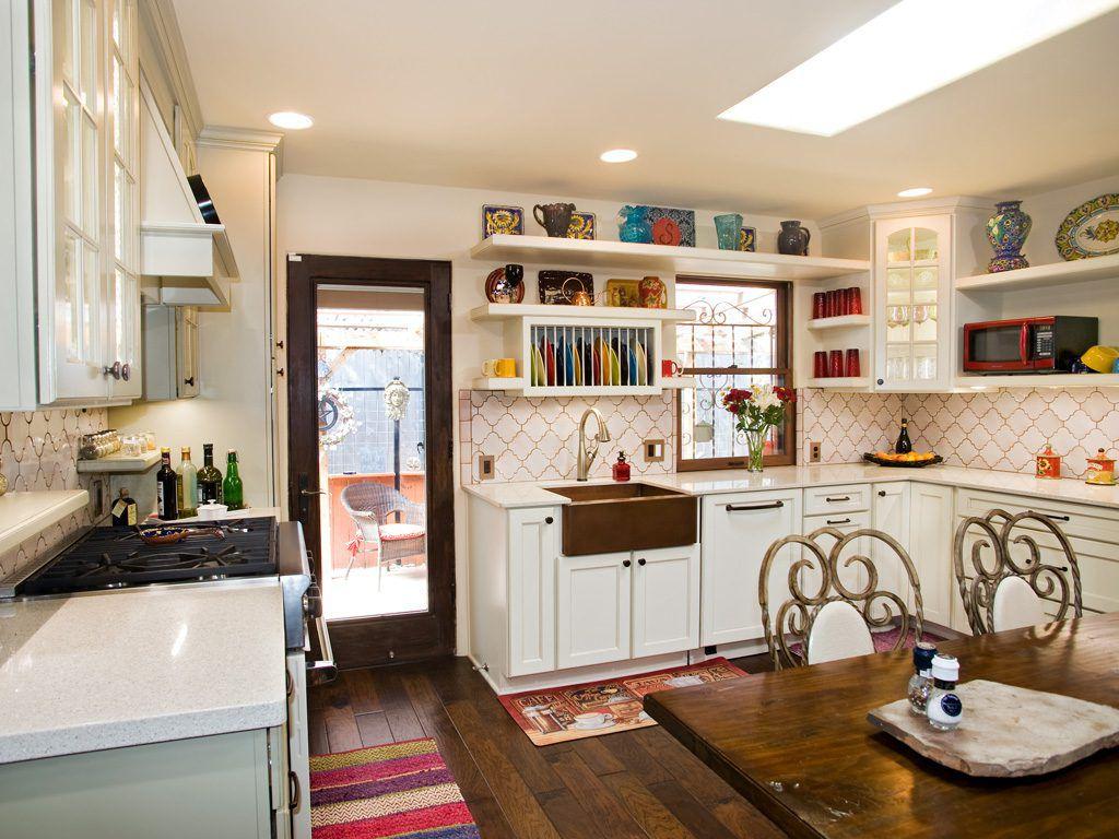 Cocina de campo francesa con gabinetes abiertos y ventanas con vista al fregadero