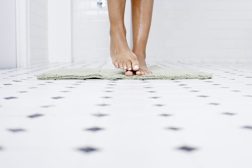 Woman standing on bathmat in tiled bathroom