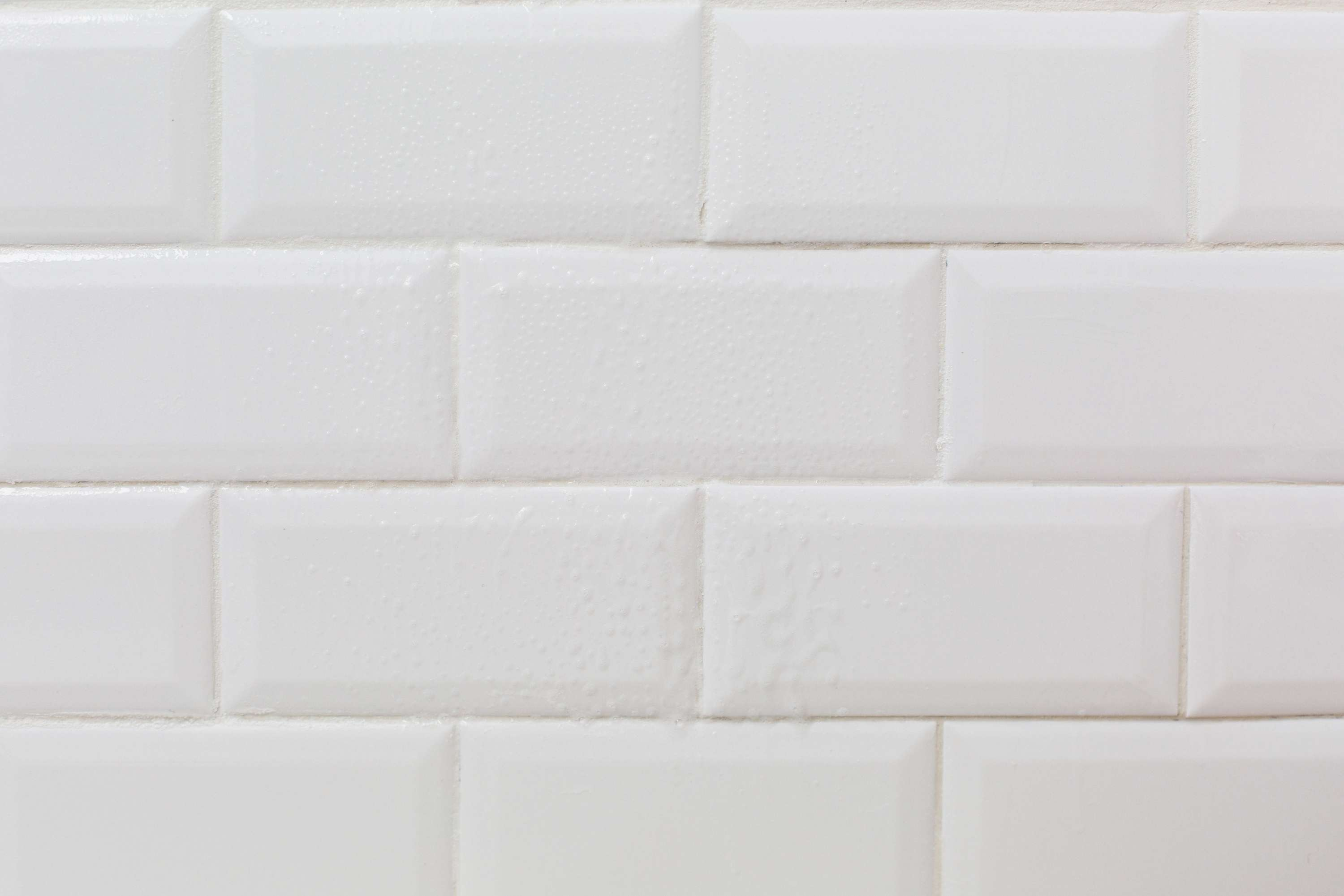White tiled wall with cleaning solution sprayed on