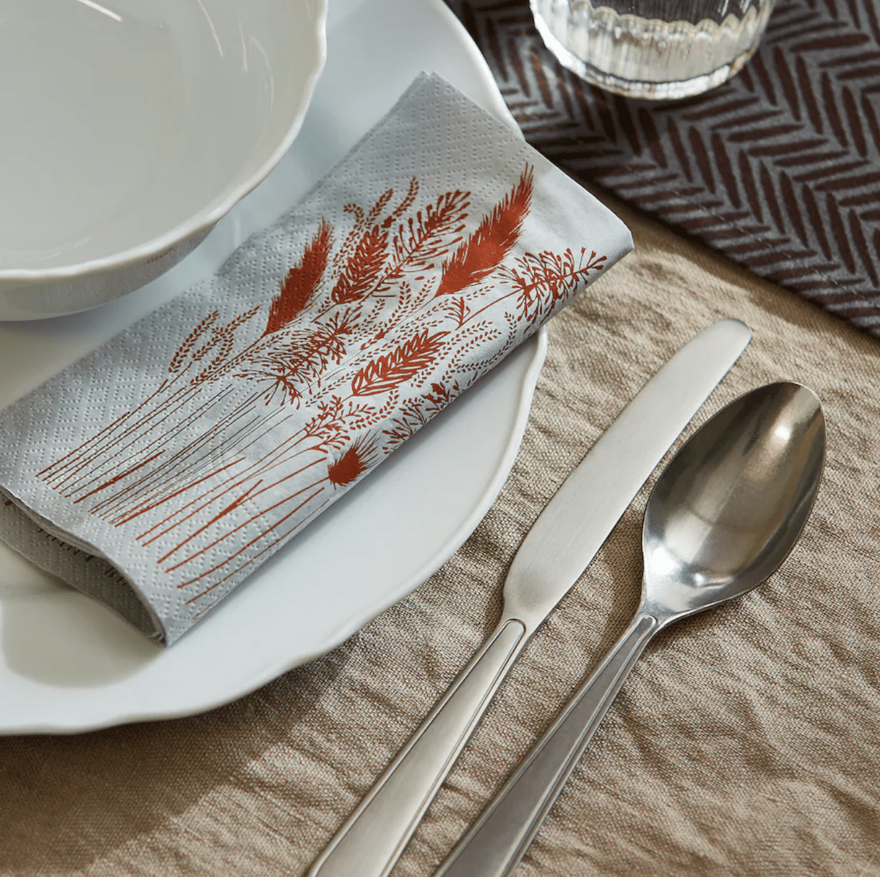 A grey and red paper napkin on a place setting