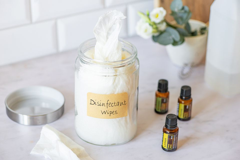 Homemade disinfectant wipes in glass jar next to essential oils