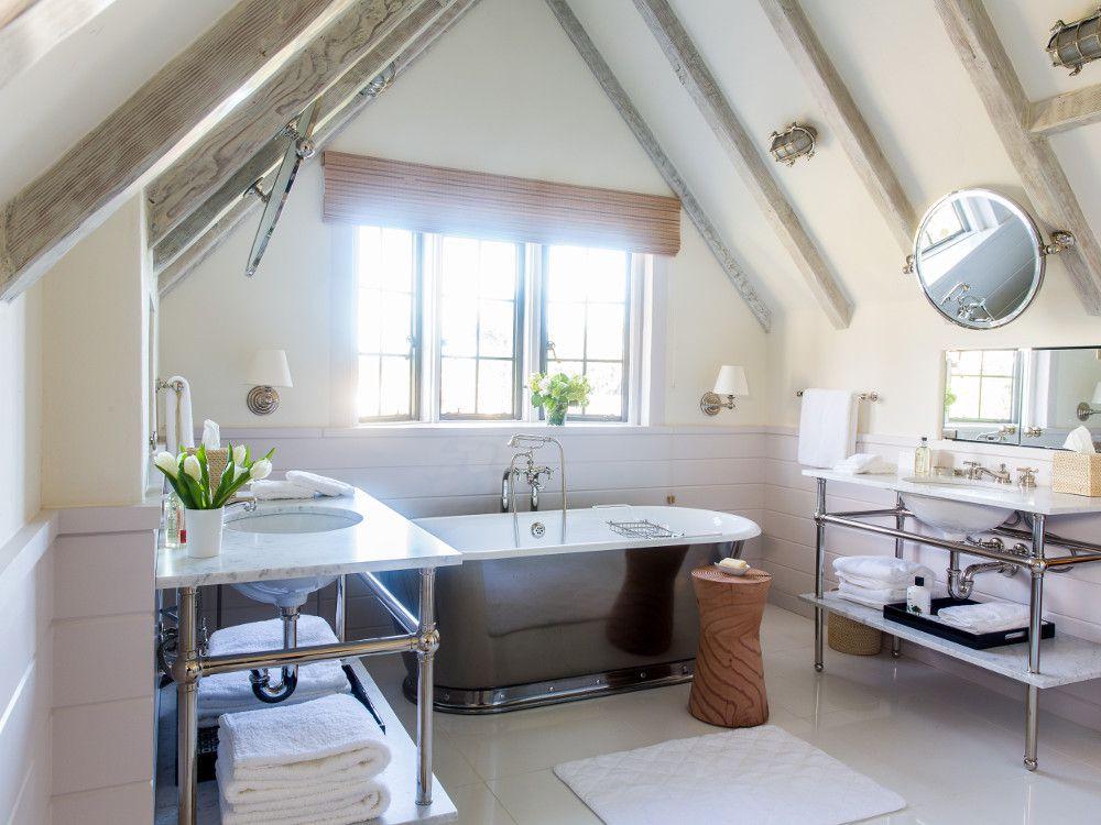 large attic bathroom with freestanding tub