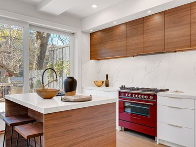 Wood kitchen with red accent stove and white marble walls