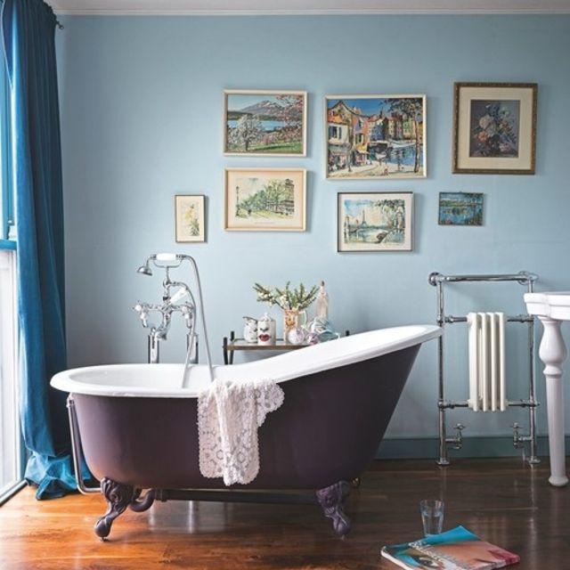bañera con patas con una pared de arte encima