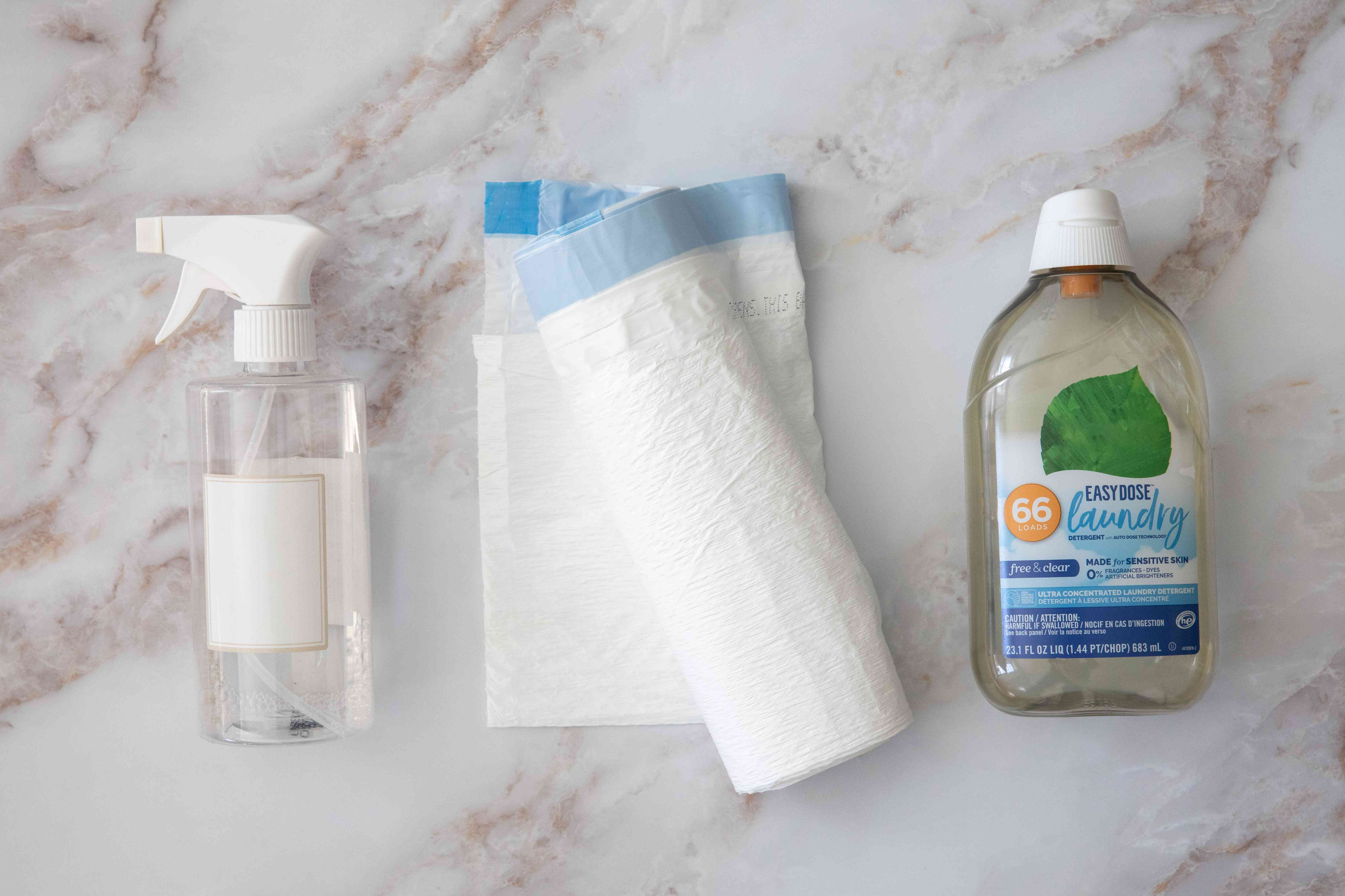 Glass spray bottle next to roll of plastic trash bag and laundry detergent bottle