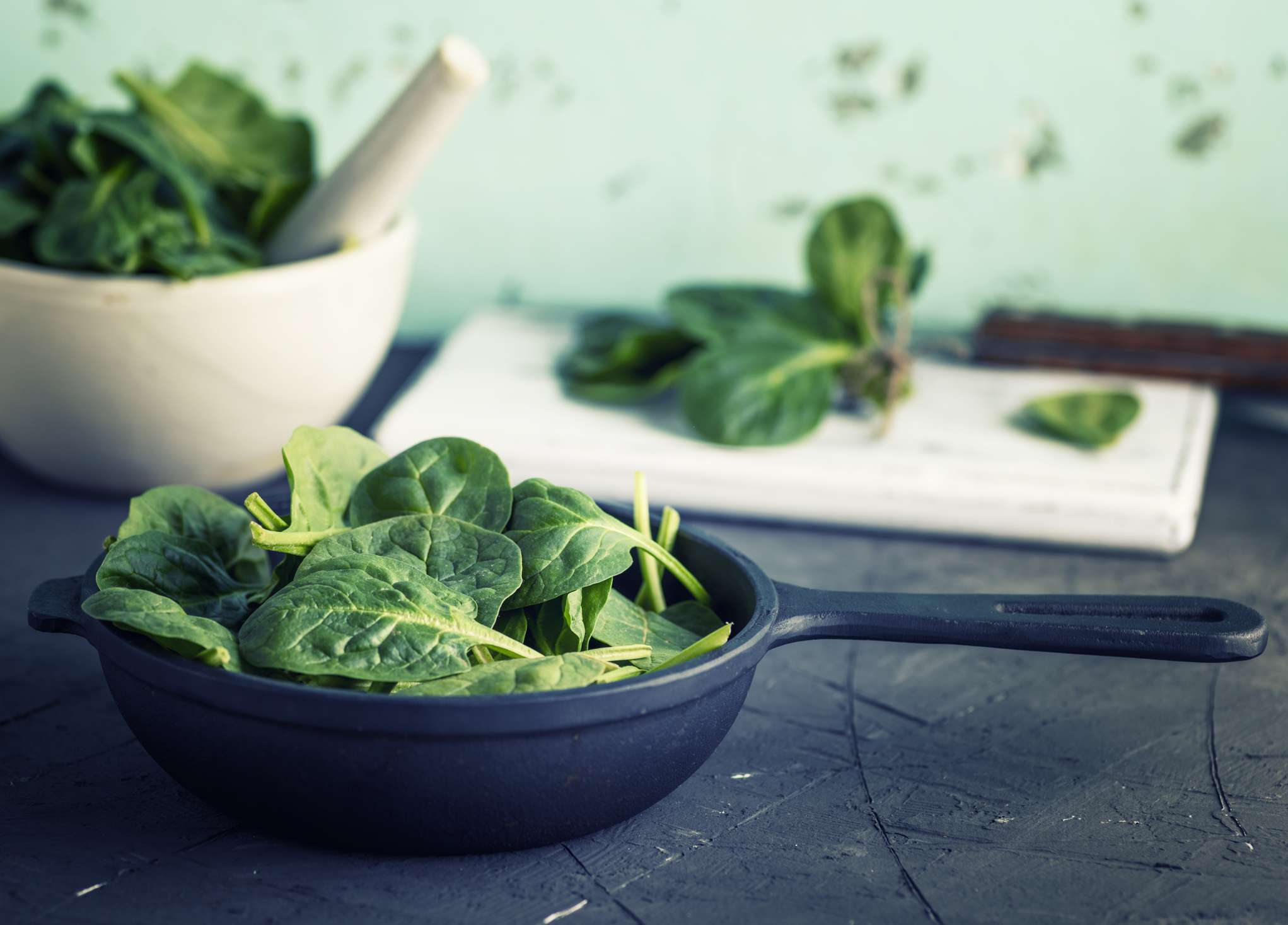 Fresh spinach in different cooking pots