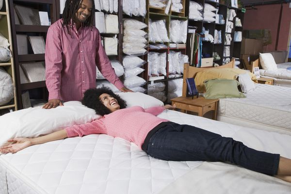 Couple shopping for a mattress at a store.
