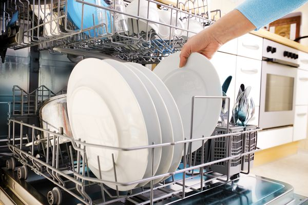 Female hand loading a dishwasher with white plates