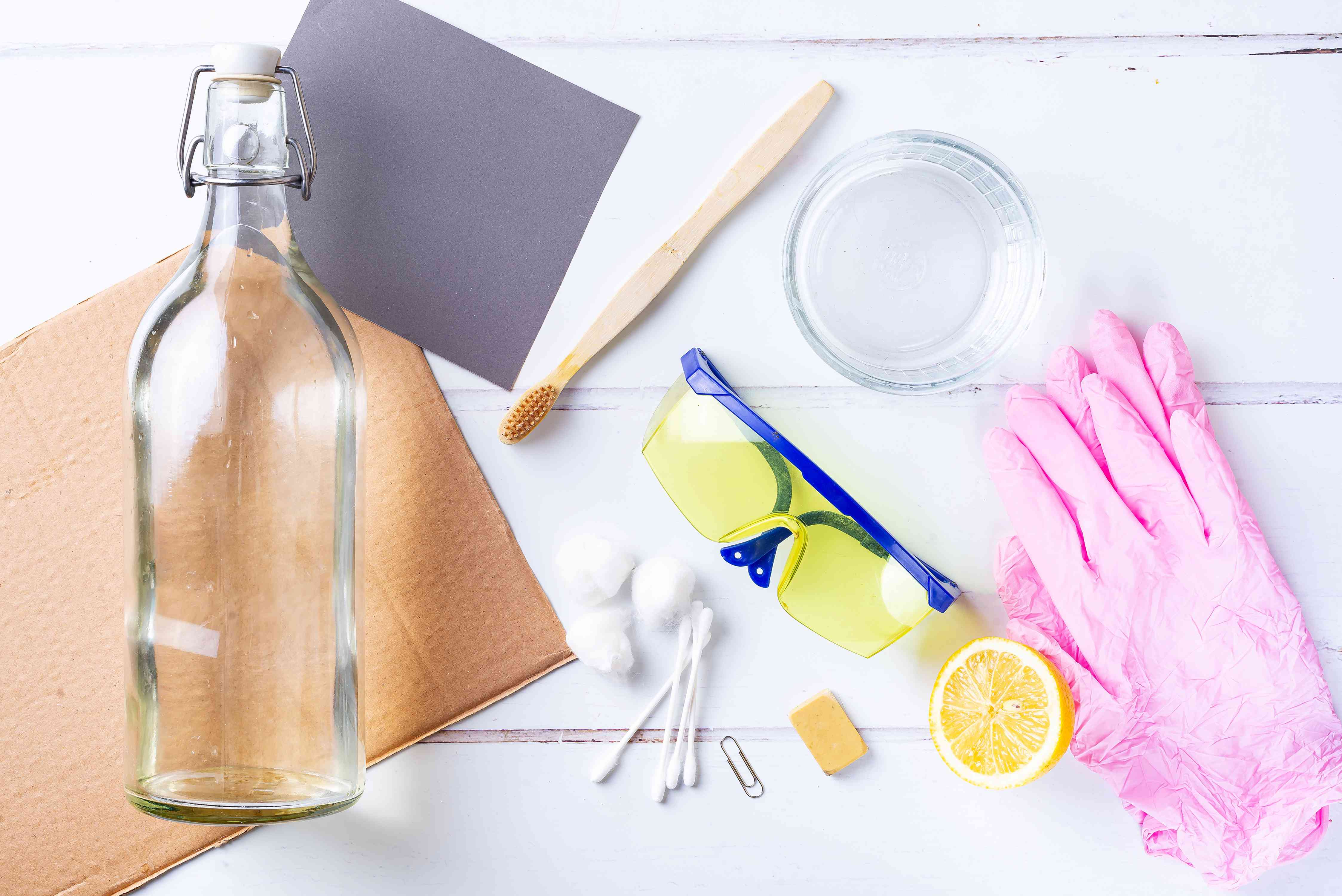 Materials and tools laid on white surface to clean battery acid