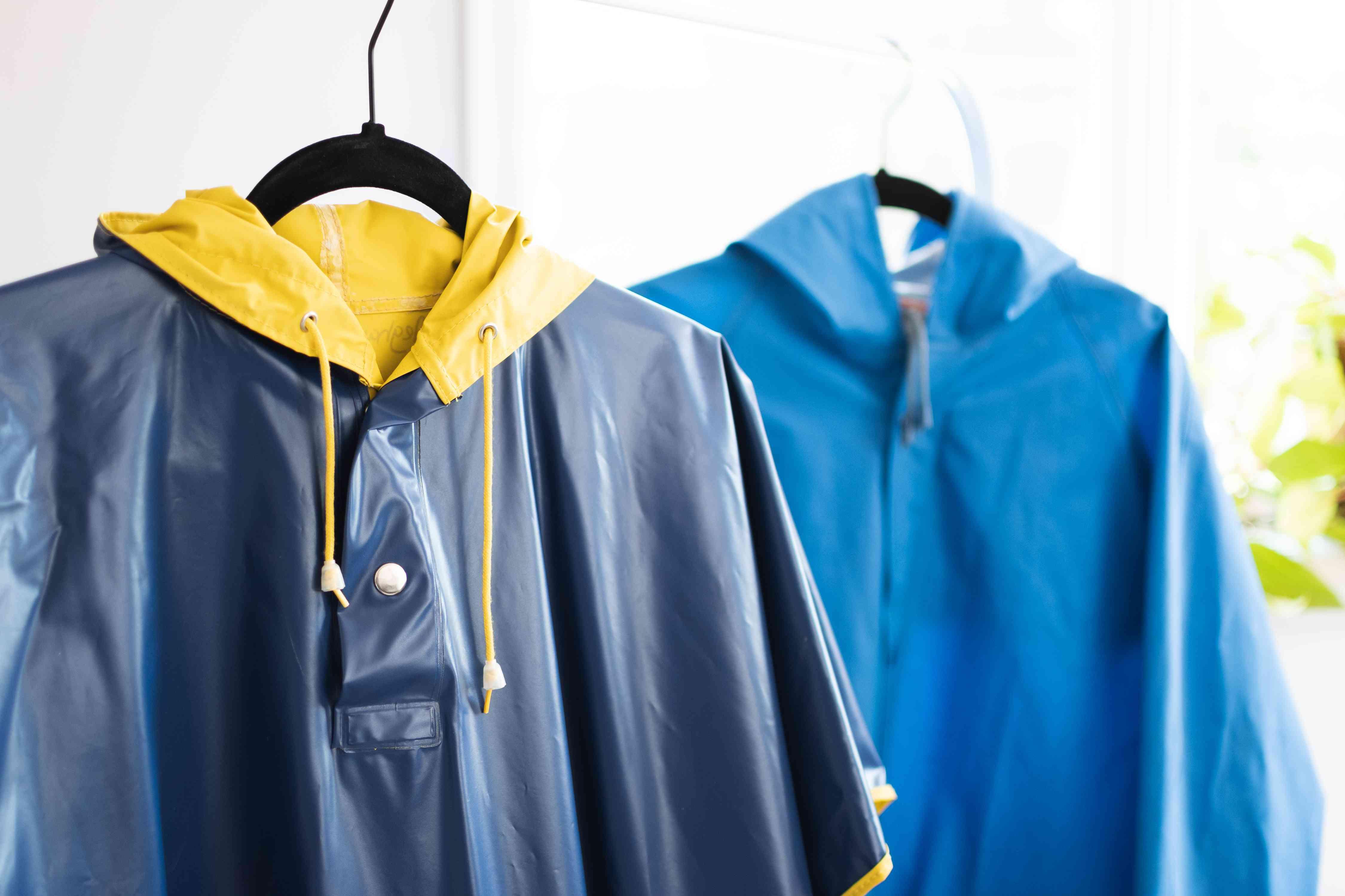 Vinyl and rubber rain coats hanging on black hangers