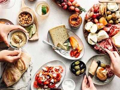 Women eating fresh Mediterranean platter on table
