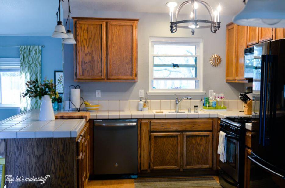 Cocina anticuada con gabinetes de roble y encimeras de azulejos