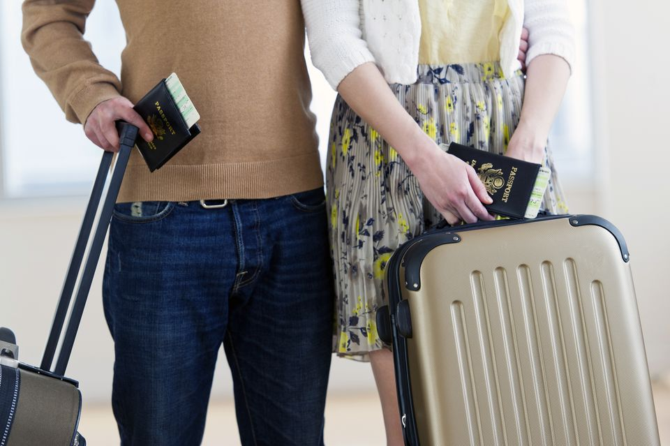 Close up of couple with luggage and passports
