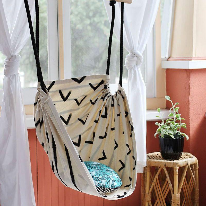 A hammock chair by a window