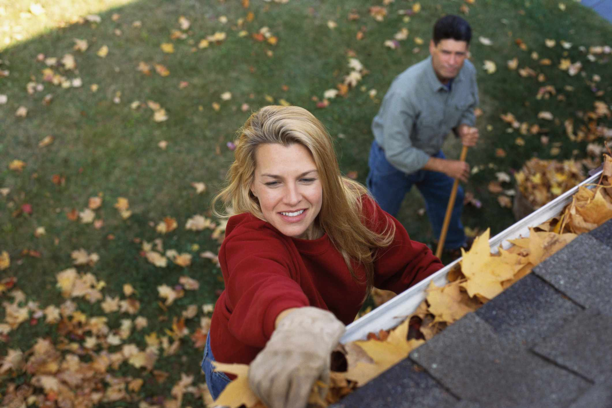 Couple cleaning gutters