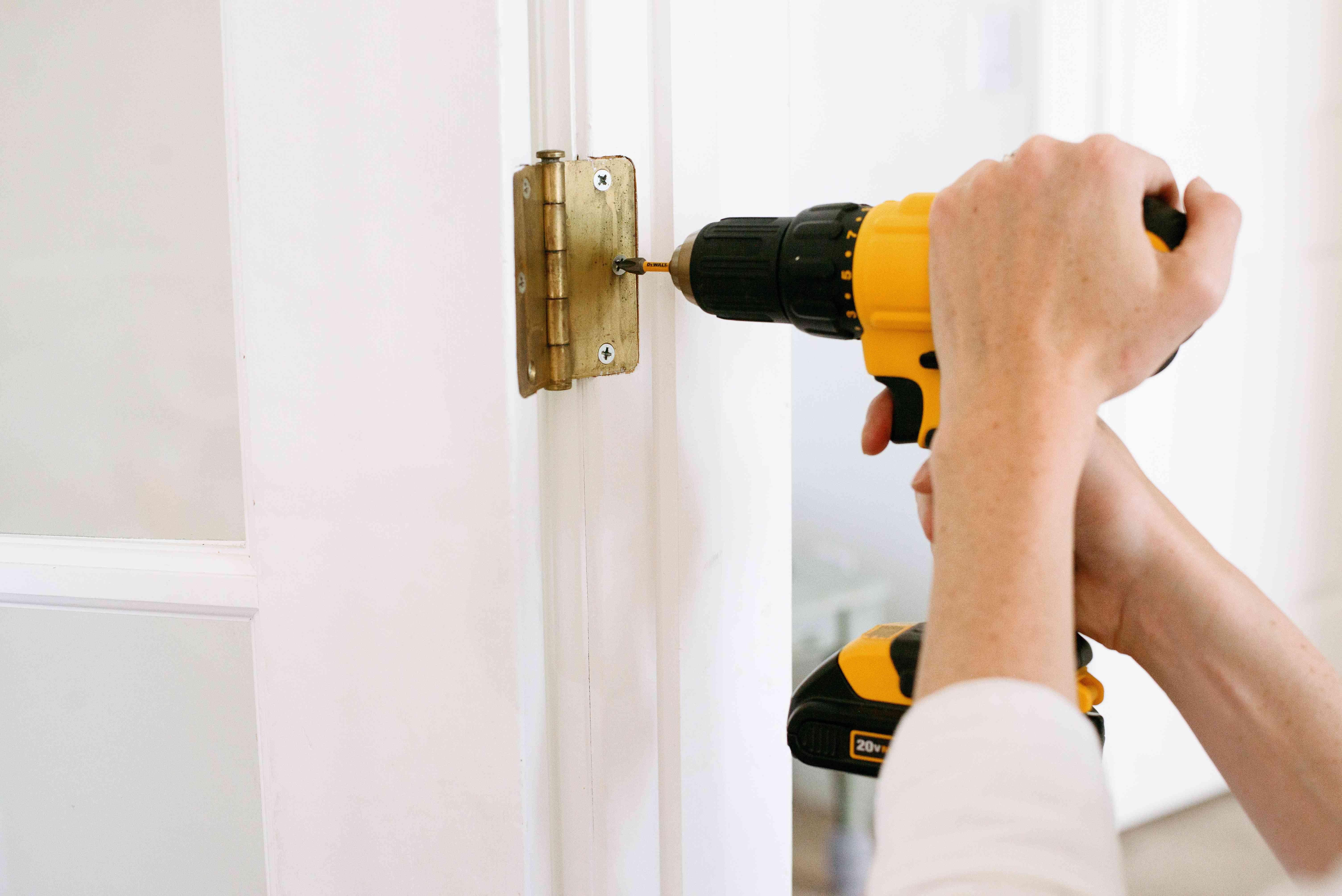 Door hinges removed with yellow electric drill