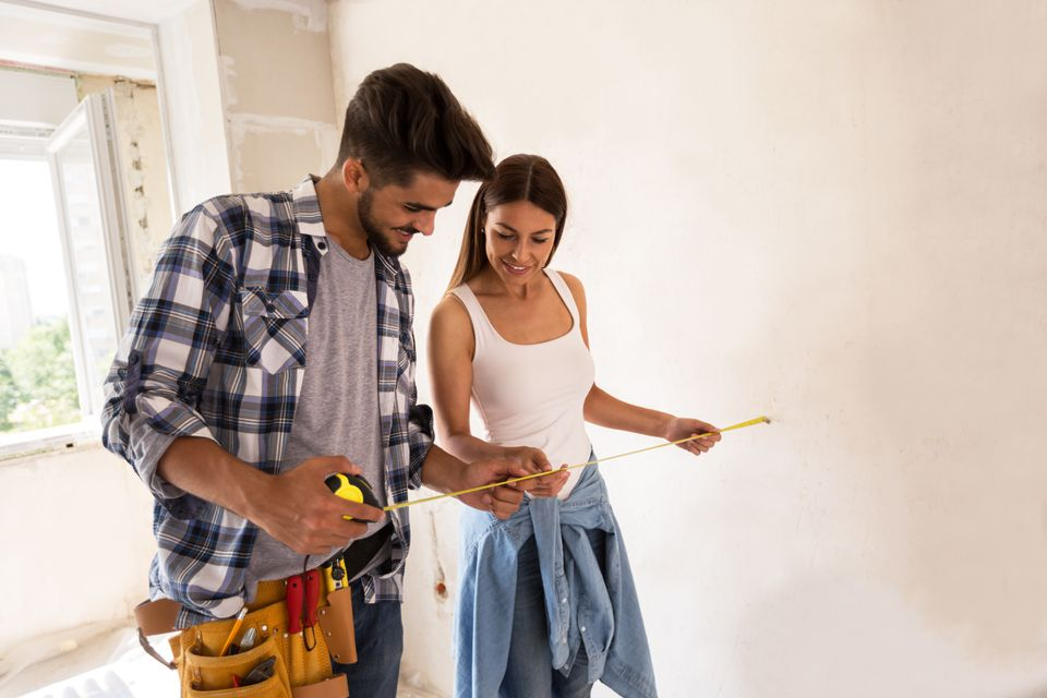 Couple using measuring tape