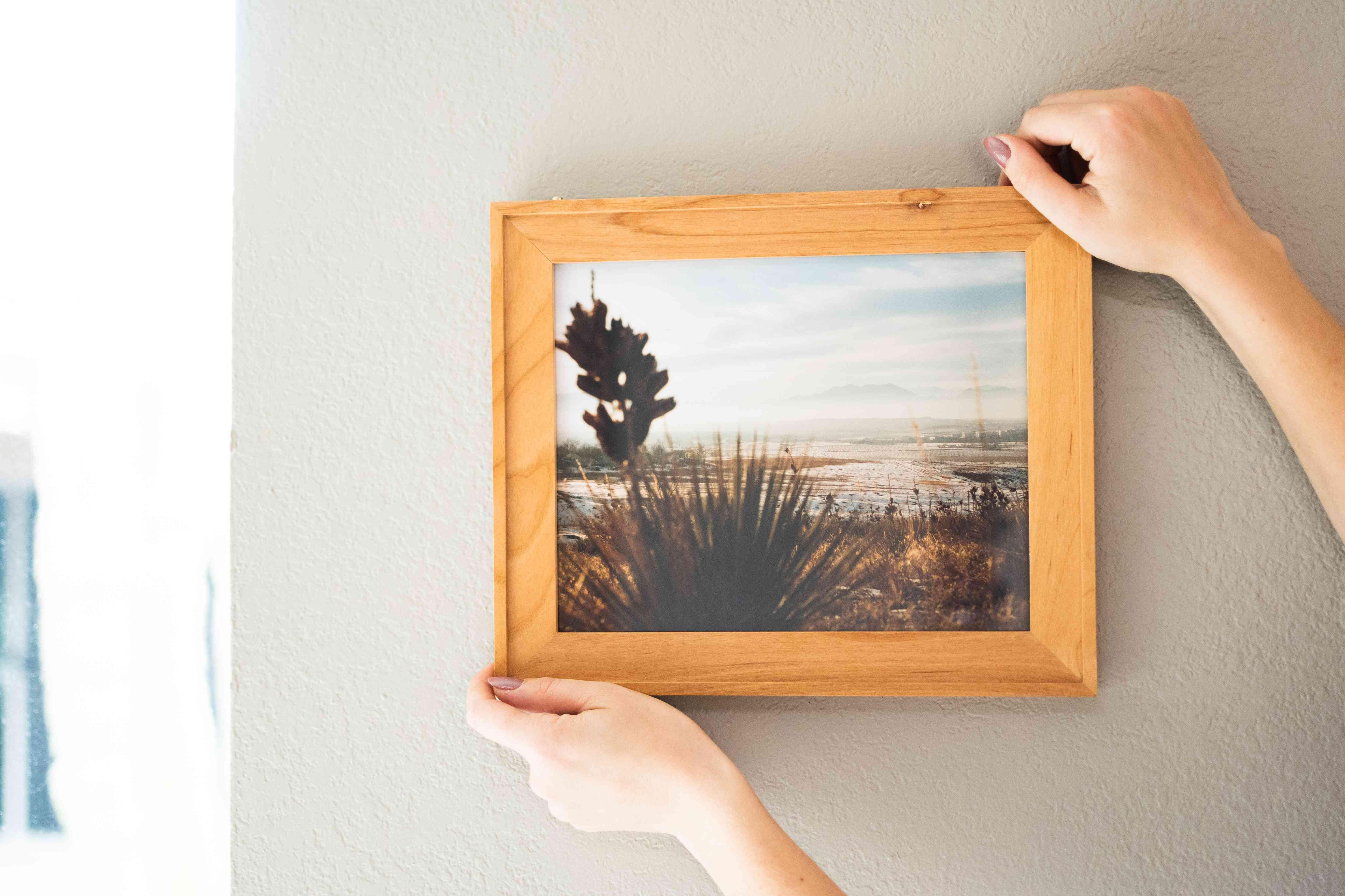 Picture being hanged on two wall hangers with hands