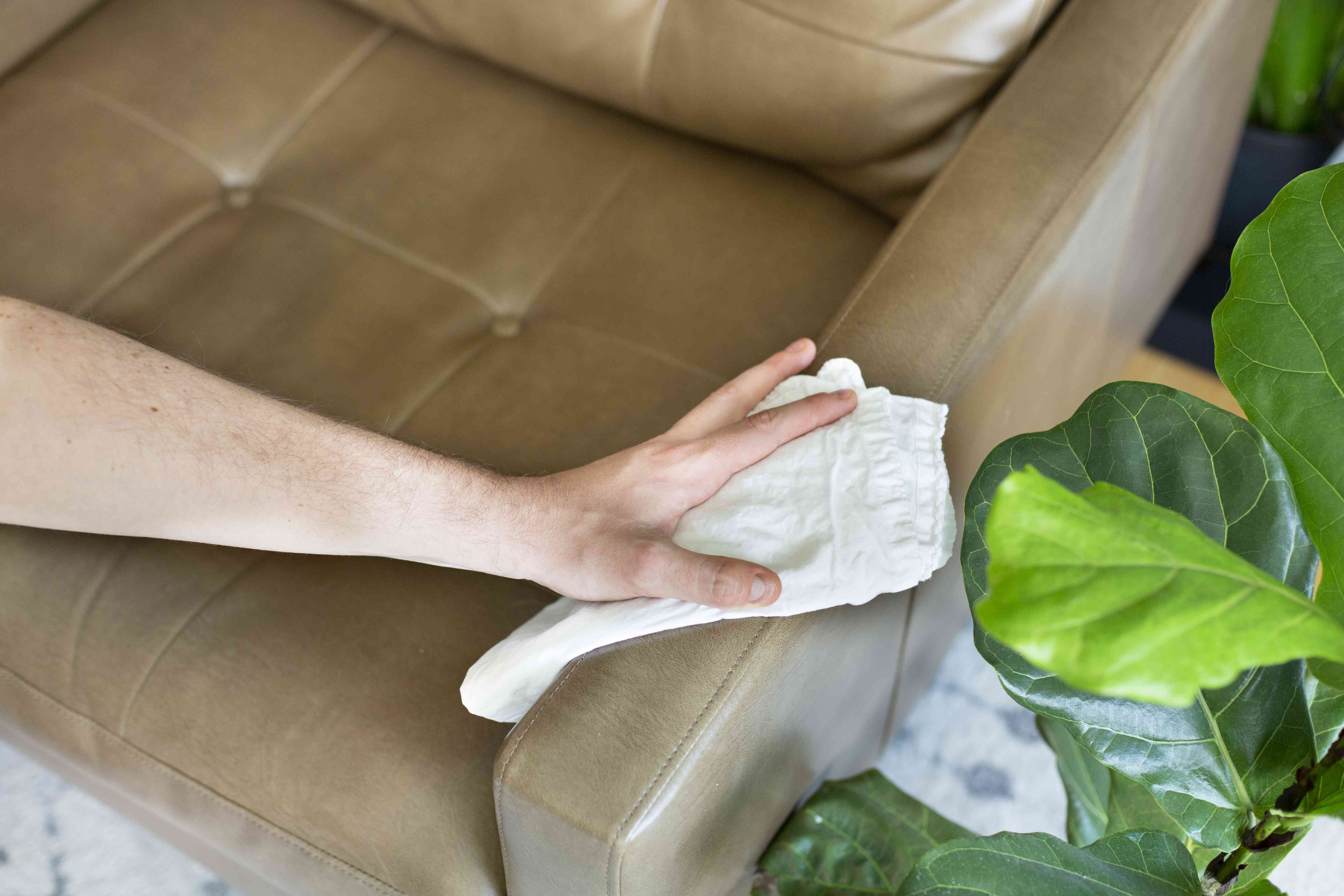 person buffing a leather chair with a dry cloth