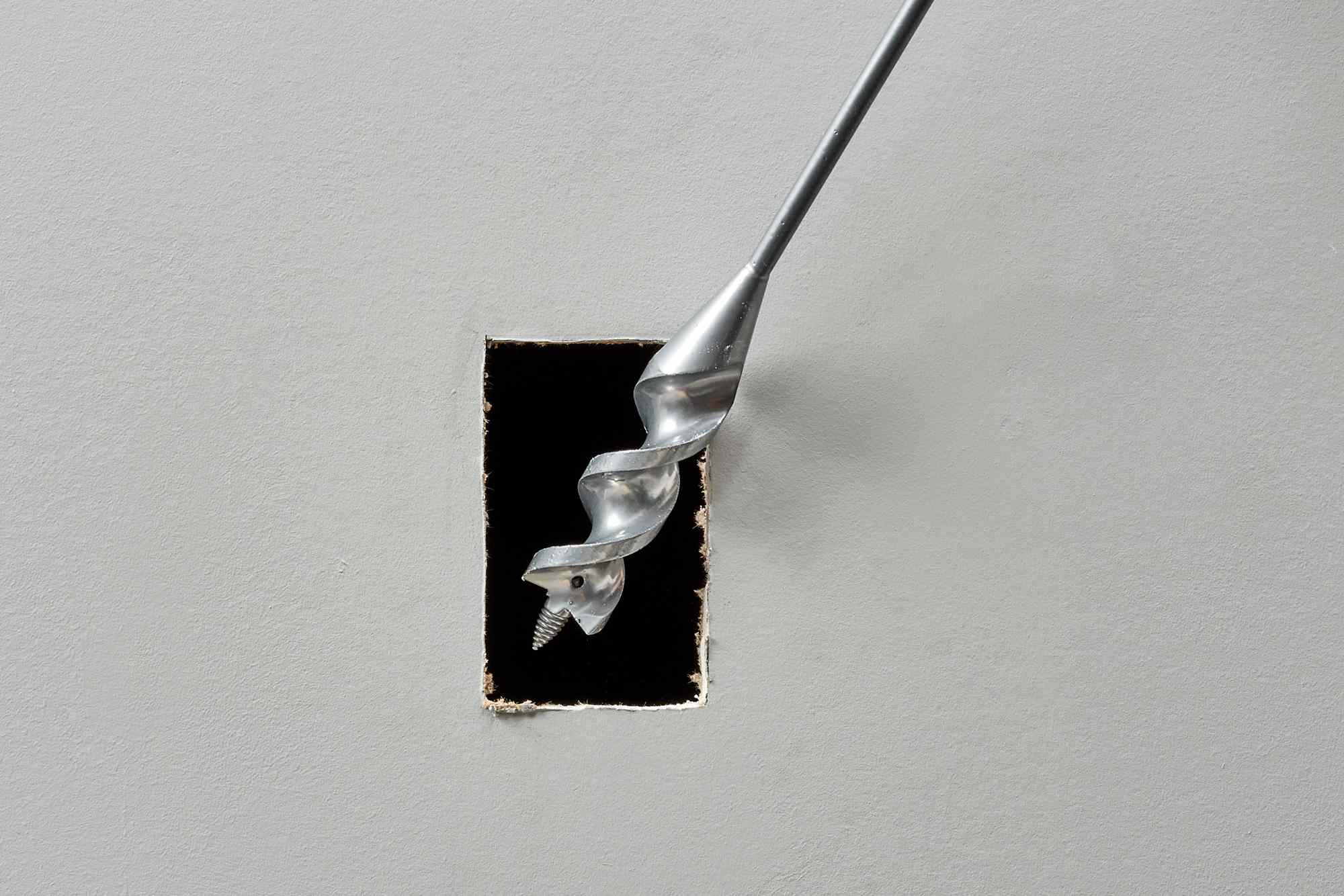 Spade bit drilling access hole in drywall hole