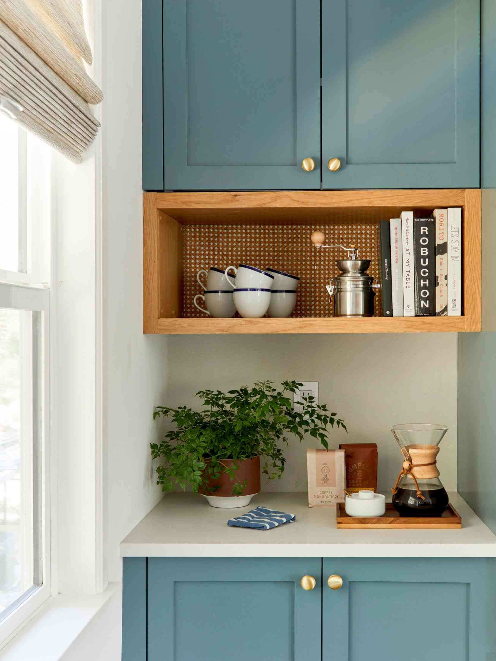 beverage station with blue cabinets, built in wooden shelf with cups and cookbooks