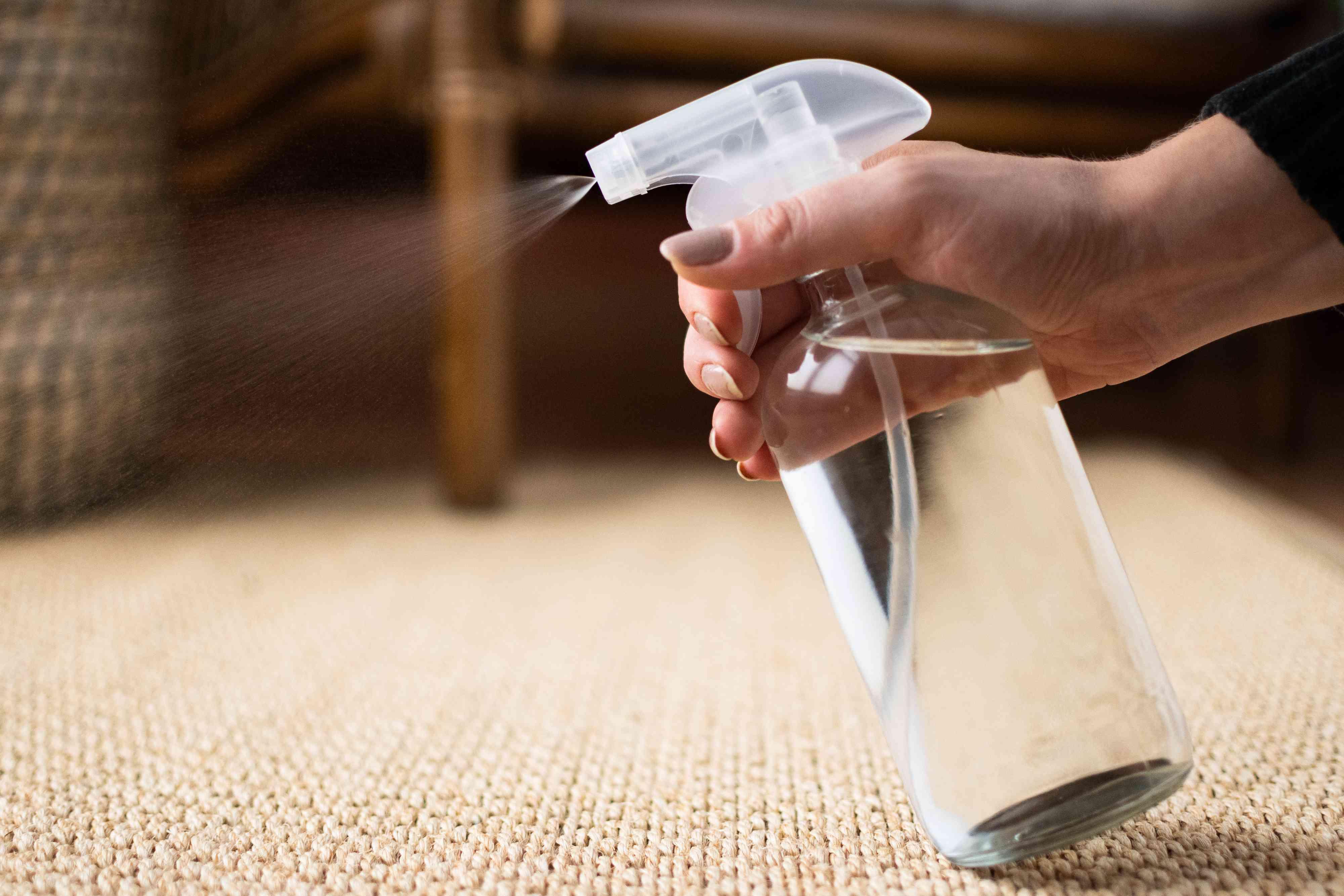 Glass bottle spraying water on sisal rug closeup