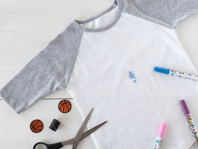 White and gray shirt with blue stain next to colored markers and scissors
