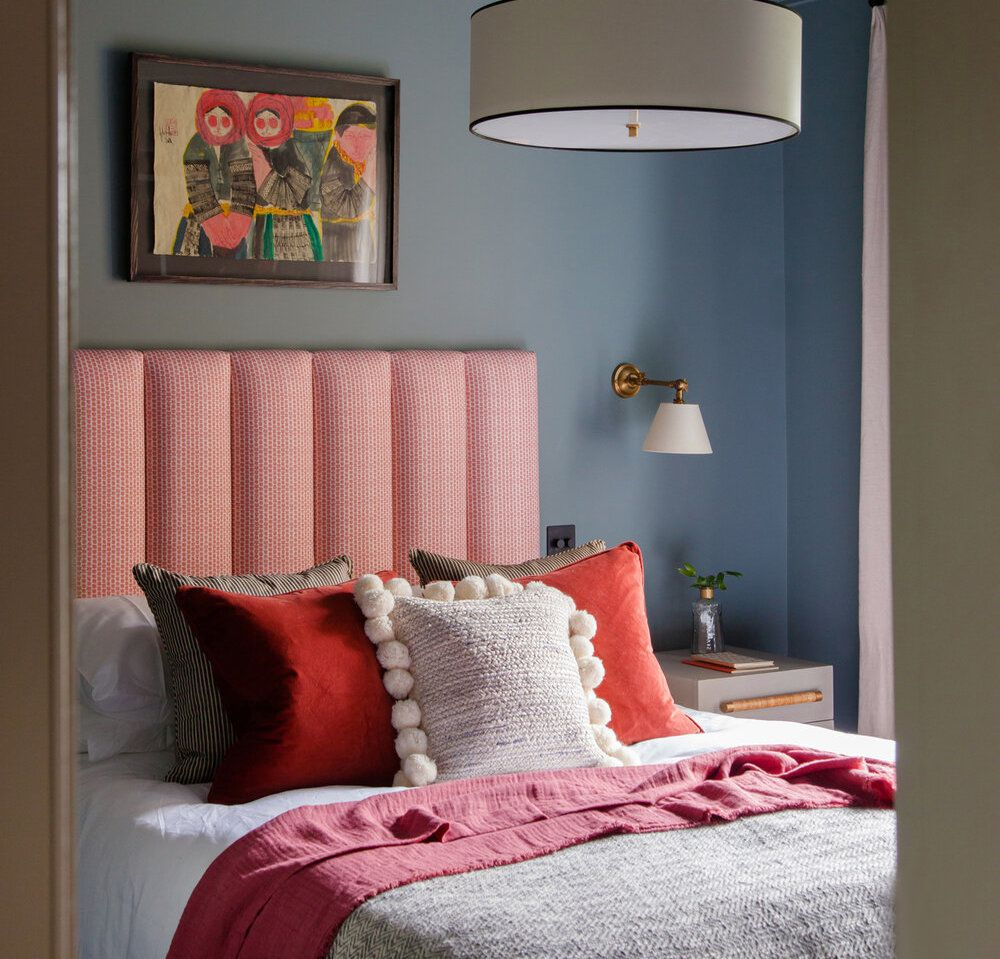 bedroom with red headboard and pillows, cornflower blue walls