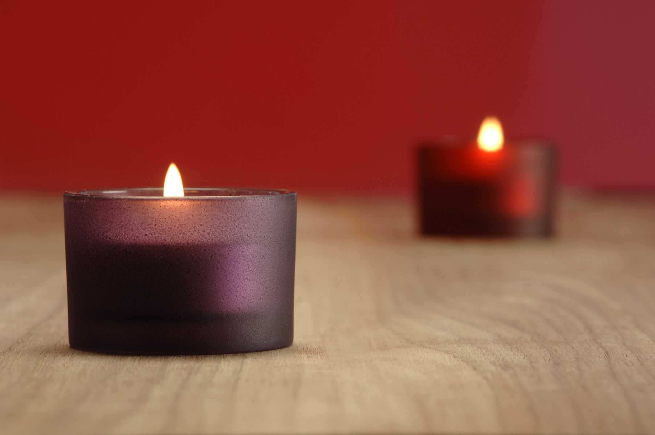 red and purple candles with red wall in the blurred background