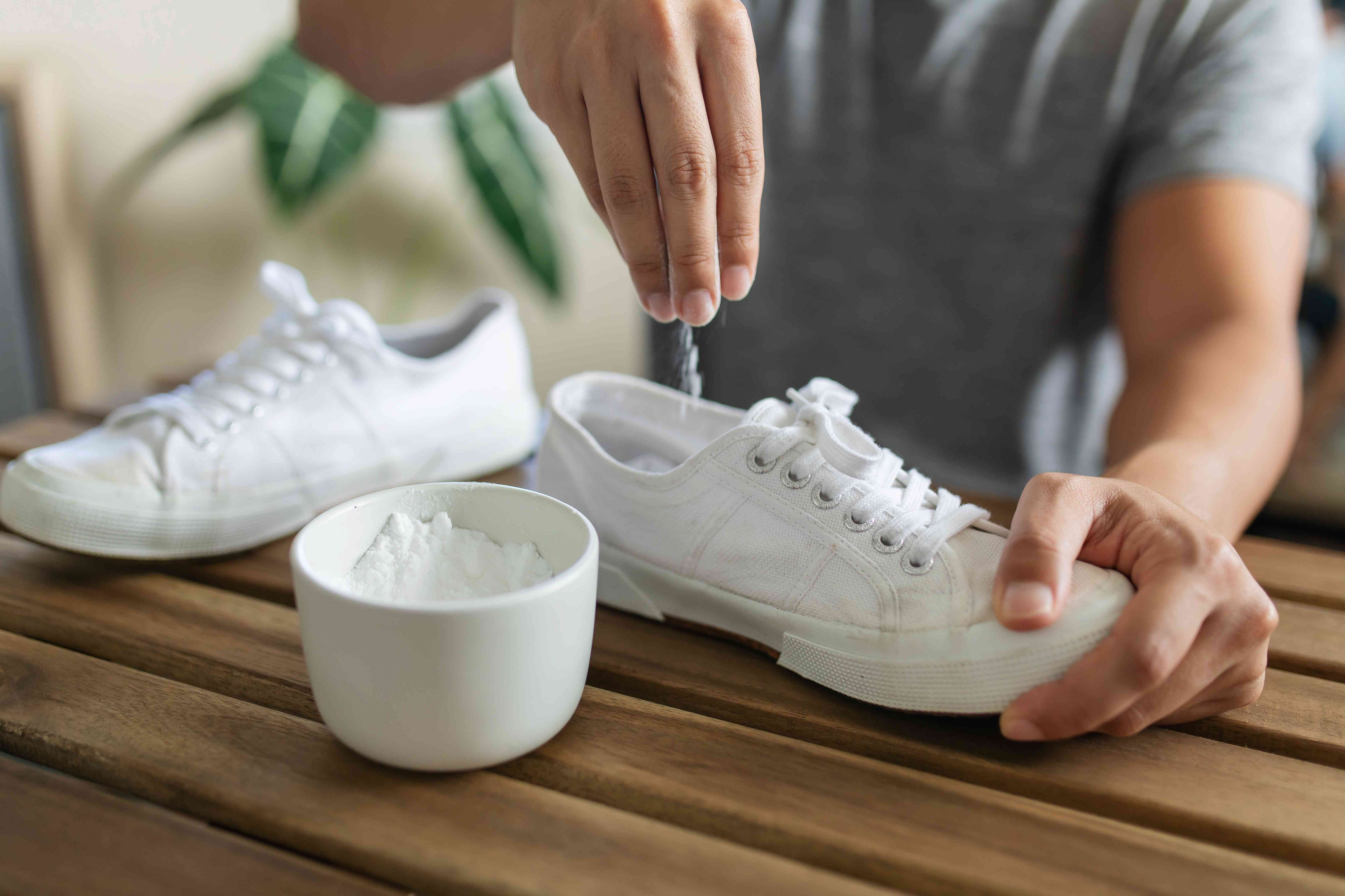 a person sprinkling baking soda inside shoes