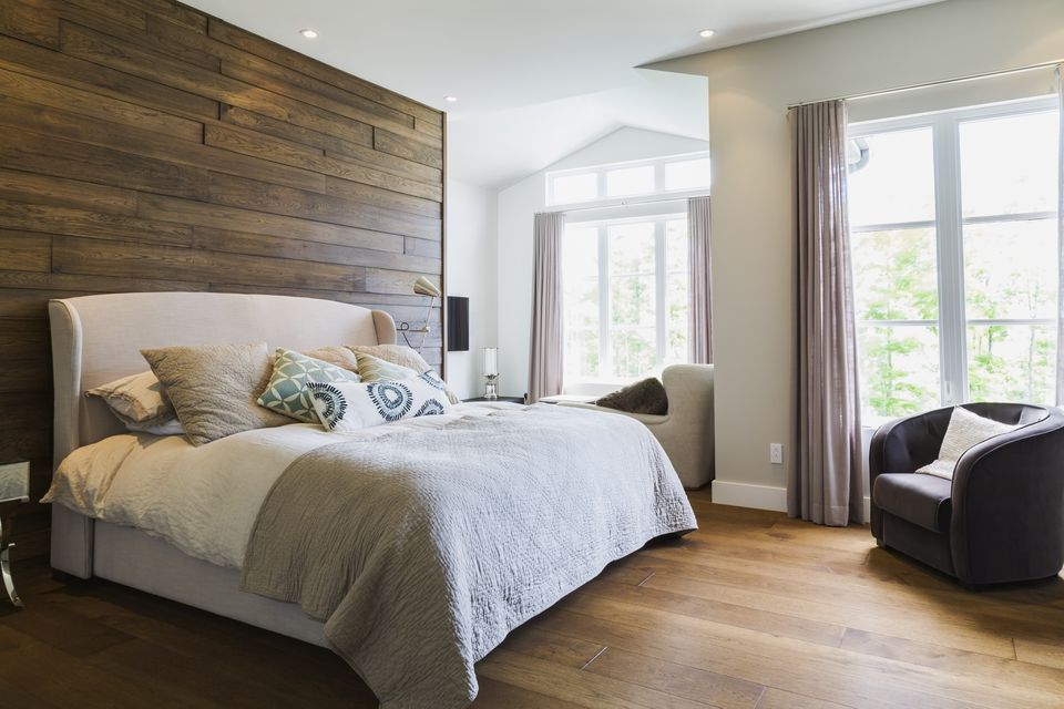 King size bed in bedroom with hickory wood floorboards