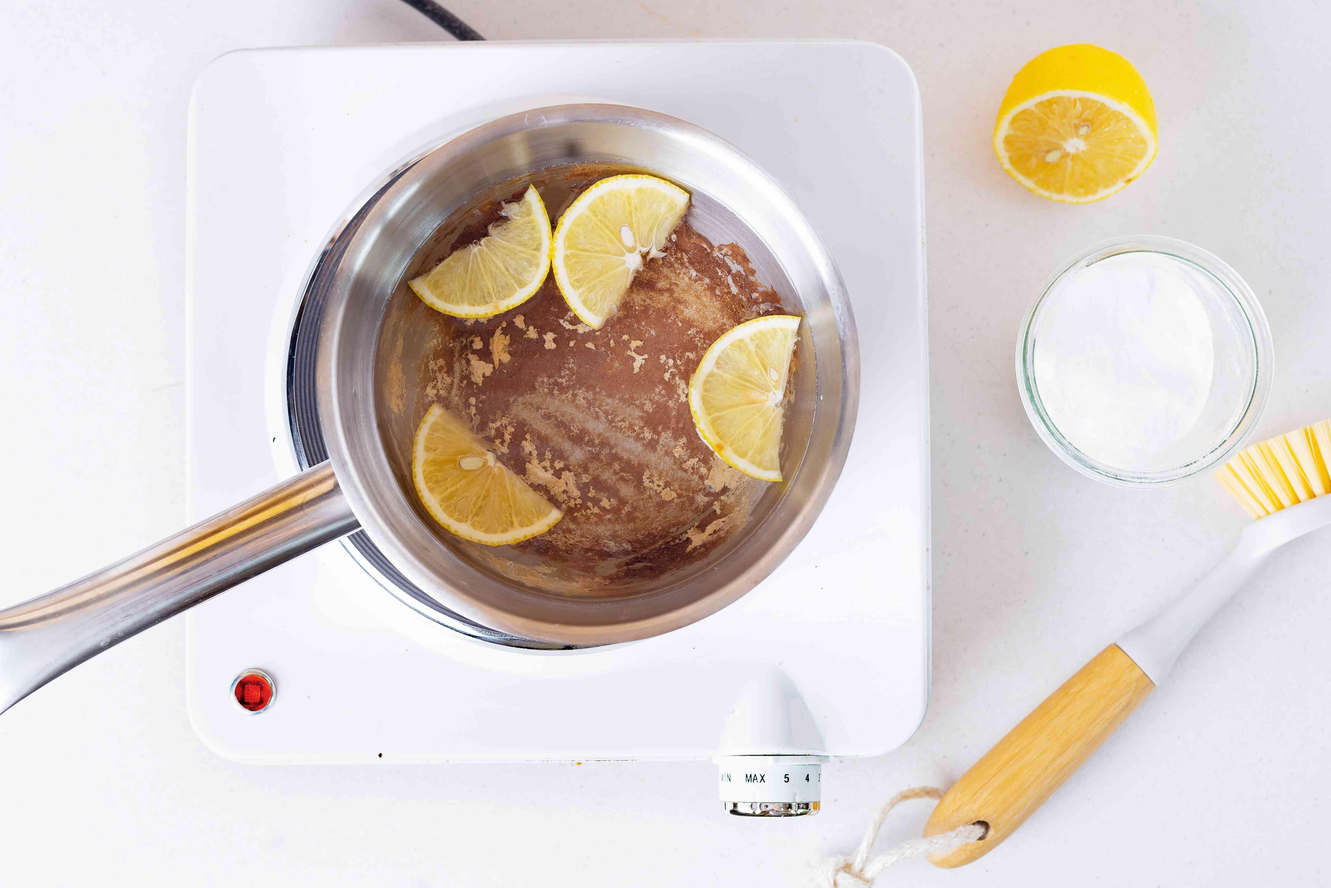 Baking soda and lemon slices in stainless steel pot heated on portable burner