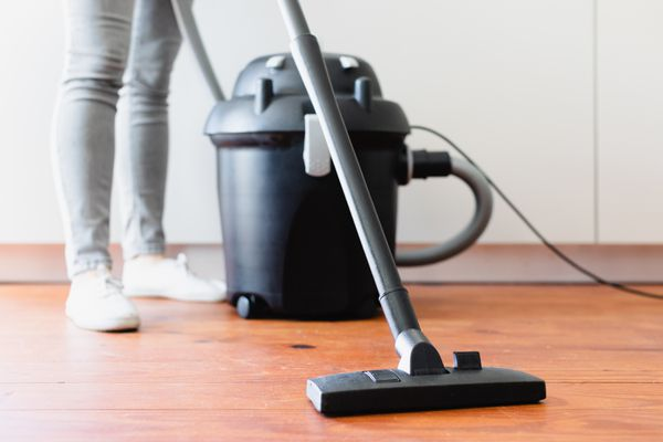 Upright vacuum cleaner with hose being used on wooden floor
