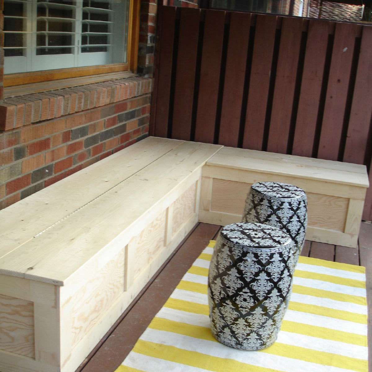 An outdoor bench and yellow rug